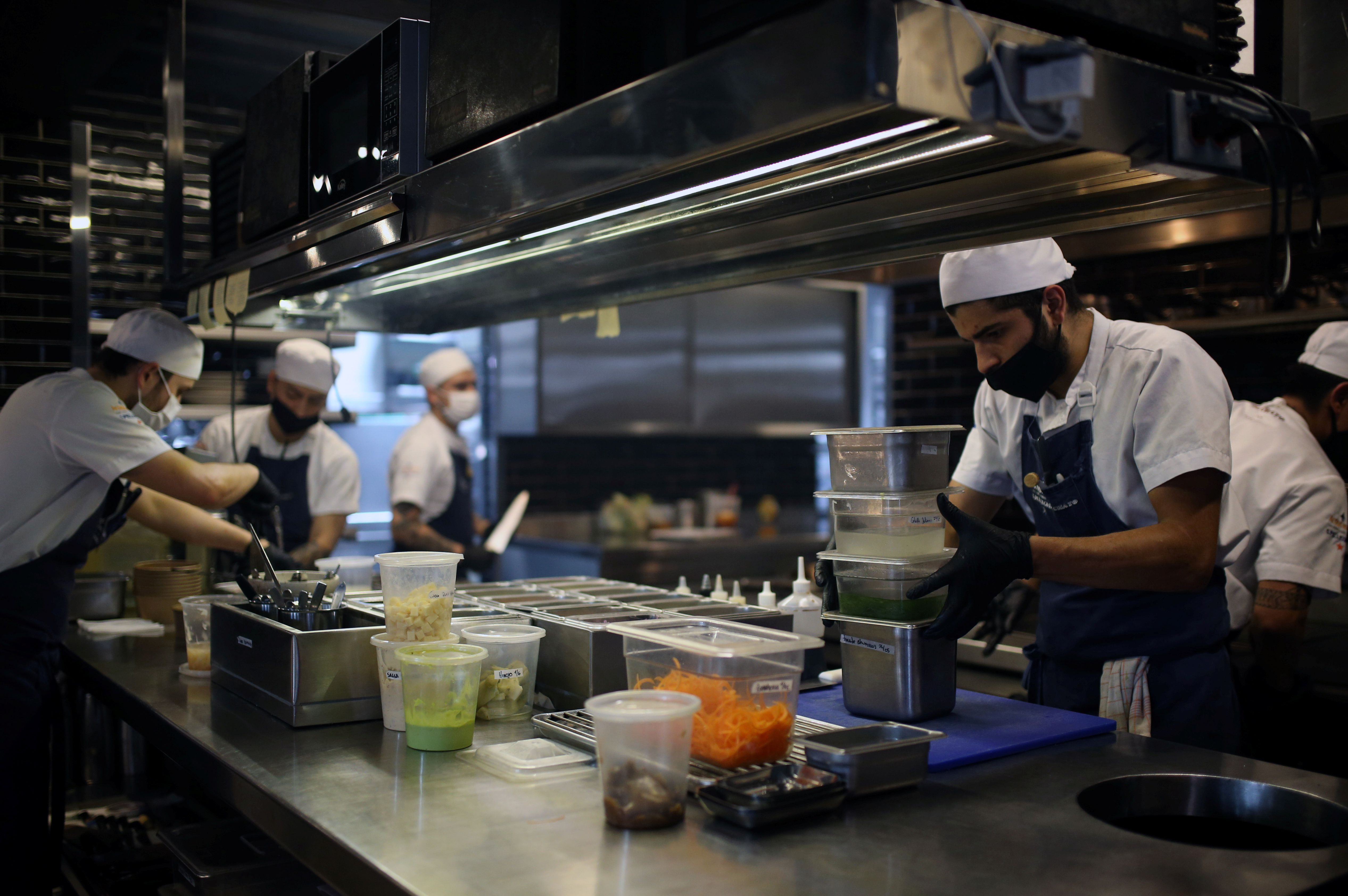 Employees of the El Chato restaurant wear face masks while preparing food for delivery, amidst the outbreak of the coronavirus disease (COVID19), in Bogota, Colombia June 2, 2020. Picture taken June 2, 2020. REUTERS/Luisa Gonzalez