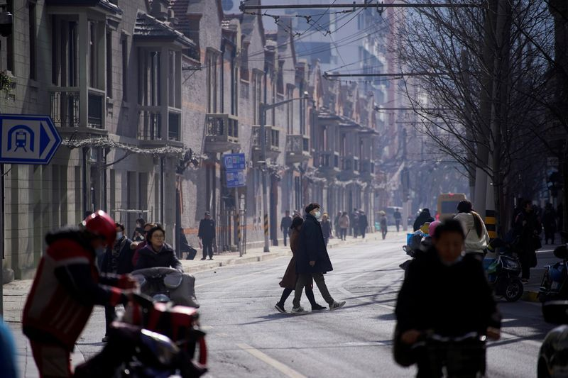 A man wearing a face mask crosses a street following the coronavirus disease (COVID-19) outbreak, in Shanghai, China January 14, 2021. REUTERS/Aly Song