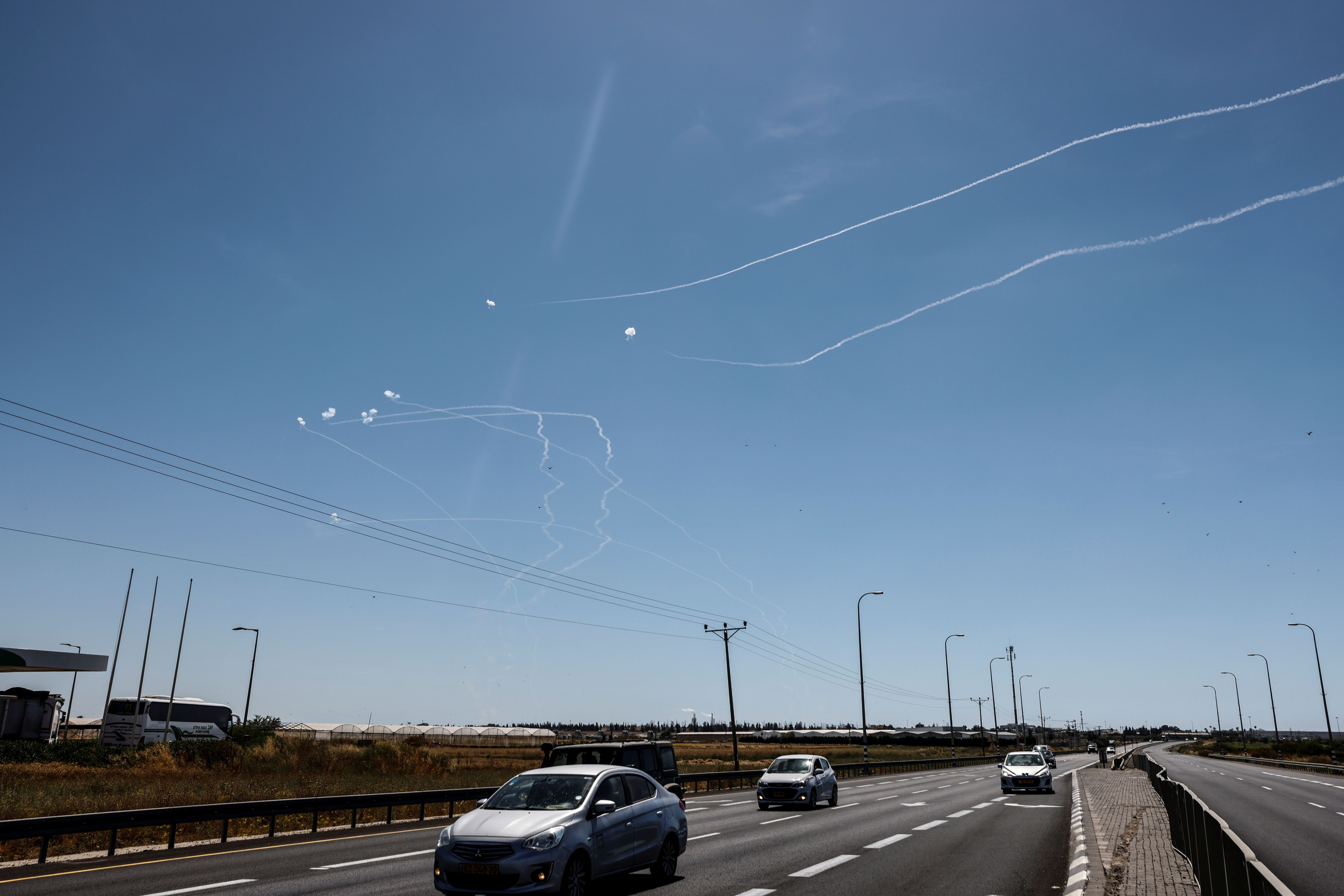 Cars drive on a main road as Israel's Iron Dome anti-missile system intercept rockets launched from the Gaza Strip towards Israel, near Ashkelon, Israel May 18, 2021. REUTERS/Amir Cohen